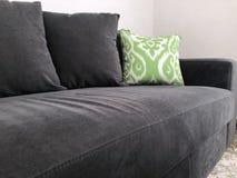 Czarna kanapa z zieleni poduszką obrazy stock