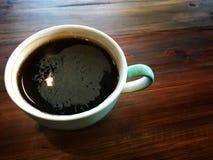 Czarna kawa Budzi się ja, Czarna kawę w bielu i zieleni filiżankę up, obraz royalty free