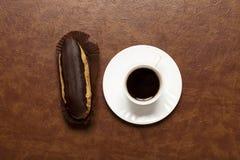 Czarna kawa, czekoladowy Eclair, kawa w białej filiżance, biały spodeczek na brązu stole, Eclair na stojaku obrazy stock