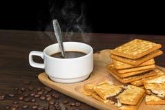 Czarna kawa, krakers i kawowa fasola na drewnie z ciepłym rankiem, zdjęcie stock