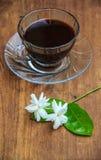 Czarna kawa na stole z Jaśminowym kwiatem Obraz Stock