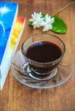 Czarna kawa na stole z starymi książkami i Jaśminowym kwiatem Zdjęcia Royalty Free