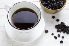 Czarna kawa w białej filiżance i kawowych fasolach z łyżką Zdjęcie Royalty Free