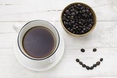 Czarna kawa w białej filiżance i kawowych fasolach z uśmiechniętą twarzą Fotografia Royalty Free