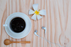 Czarna kawa w białej filiżance z białym plumeria kwiatem na drewnianym b Fotografia Stock