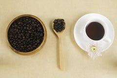 Czarna kawa w białej filiżance z kawowymi fasolami w drewno talerzu Zdjęcia Stock