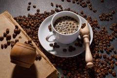 Czarna kawa w filiżance na tle kawowe fasole w składzie z akcesoriami obrazy stock