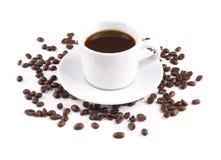 Czarna kawa w kubku z spodeczek kawowymi fasolami jest rozpraszającym iso zdjęcie stock