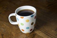 Czarna kawa w polki kropki kubku Fotografia Stock