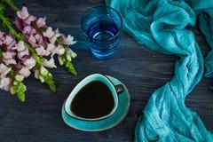 Czarna kawa w turkusowej filiżance, szkle woda i kwiatach na czarnym tle, Odgórny widok, depresja klucz, bezpłatna przestrzeń obraz stock