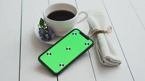 Czarna kawa z mądrze telefonem na białym nieociosanym drewnianym stole, zdjęcie wideo