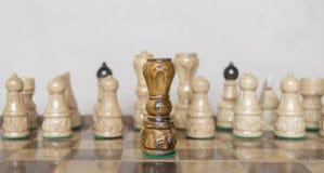 Czarna królowa przed biel postaciami na szachy stole Zdjęcie Stock