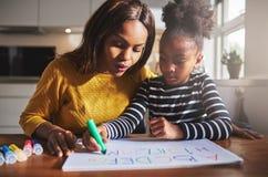 Czarna matka i dziecko robi pracie domowej Obrazy Royalty Free