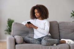 Czarna nastoletnia dziewczyna relaksuje na leżance używać smartphone obrazy stock