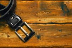 Czarna patka z klamrą na starym drewnianym tle zdjęcie stock