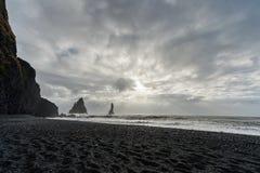 Czarna piasek plaża Reynisfjara w Iceland Skały w wodzie fale oceanu się fala pierwszoplanowe wietrzny zachmurzone niebo Fotografia Royalty Free