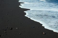 Czarna piasek plaża z białą ocean pianą zdjęcie royalty free