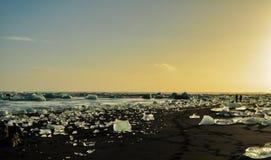 Czarna plaża zakrywająca lodowym kamieniem fotografia stock