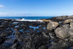 Czarna powulkaniczna skała na hawajczyk plaży blisko Kona Tidepools wśród skały Fale i ocean w tle zdjęcie royalty free