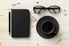 Czarna pusta dzienniczek pokrywa, czarna filiżanka kawy i szkła na drewnie, Obraz Stock