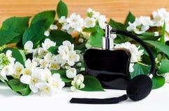 Czarna rocznika pachnidła butelka z atomizatorem na białym stole Jaśminowy kwiatu okwitnięcia tło Obrazy Stock