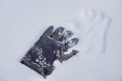 Czarna rzemienna rękawiczka w śniegu odcisk w śniegu znajdować ślad obraz stock