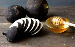 Czarna rzodkiew z miodem na drewnianym tle zdjęcie royalty free
