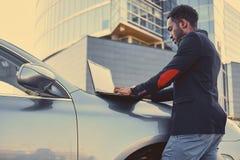 Czarna samiec używa laptop na samochodowym ` s kapiszonie zdjęcia stock