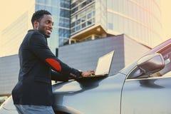 Czarna samiec używa laptop na samochodowym ` s kapiszonie obraz stock