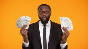 Czarna samiec w eyeglasses pokazuje wiązki gotówka, zysk, lukratywny biznes zbiory wideo