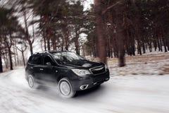 Czarna samochodowa prędkości przejażdżka z na drodze przy zima dniem Obrazy Stock