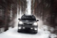 Czarna samochodowa prędkości przejażdżka z na drodze przy zima dniem Zdjęcie Stock