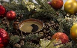 Czarna silna kawa w filiżance wśród kawowych fasoli, Bożenarodzeniowa jodła t Zdjęcie Stock