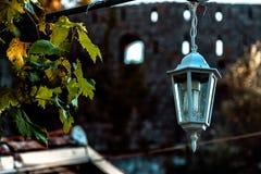 Czarna stara rocznik lampa na ściana z cegieł z dekoracyjnymi świeczkami inside przy starym grodzkim domem fotografia royalty free