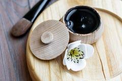 Czarna substancja w drewnianym słoju na drewnianym tle zdjęcia royalty free