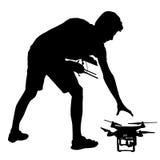 Czarna sylwetka mężczyzna działa bezpilotową quadcopter wektoru ilustrację royalty ilustracja