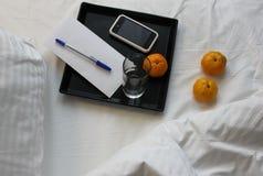 Czarna taca z szkłem woda, smartphone, koperta z piórem i tangerines na białym łóżku, Fotografia Royalty Free