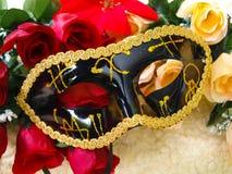 Czarna Wenecka maska z złocistymi dekoracjami na kolorowych różach, fotografia royalty free