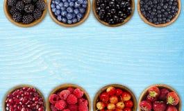 Czarne, błękitne i czerwone jagody, Czernicy, czarne jagody, rodzynki, czarne jagody, truskawki, granatowiec; wiśnie w drewnianym Obraz Royalty Free