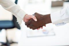 Czarne biznesmena chwiania ręki z caucasian bizneswomanem Zdjęcie Stock