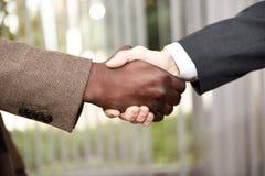 Czarne biznesmena chwiania ręki z caucasian jeden Obrazy Stock