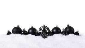 Czarne boże narodzenie piłki z śniegiem odizolowywającym na białym tle fotografia royalty free