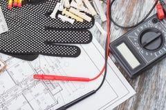 Czarne budów rękawiczki, rysunki i multimeter, drewniany tło Zdjęcie Stock