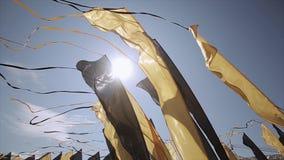 Czarne i żółte flaga z taśmami macha od wiatru w lato słonecznym dniu festiwale Błękitny bezchmurny niebo zdjęcie wideo