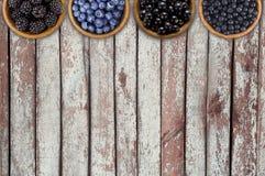 Czarne i błękitne jagody Czernicy, czarne jagody, rodzynki i czarne jagody w, drewniani puchary Zdjęcie Stock