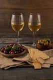Czarne i zielone oliwki słuzyć w zbiorniku krakers z wineglass Obraz Royalty Free