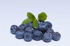 Czarne jagody, błękitne jagody czarne jagody z zielonymi liśćmi na białym tle Obrazy Royalty Free