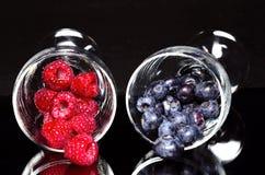 Czarne jagody i malinki fotografia stock
