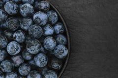 Czarne jagody na czerń kamienia tle zdjęcia stock