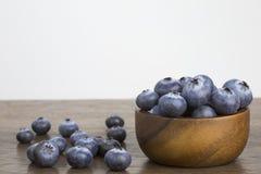 Czarne jagody w drewnianym pucharze na drewnianym stołowym białym tle kopiują Zdjęcie Stock